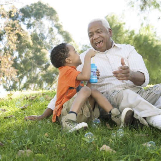 Older man and young child blowing bubbles in a field