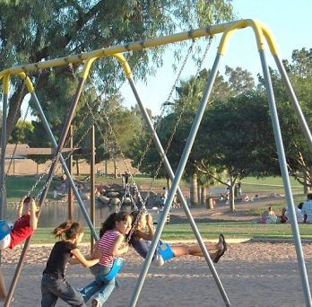 Children play on a swing set in the foreground. In the background, children and families play in the park.